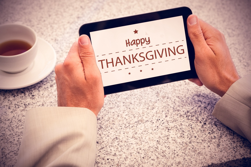 Businessman holding small tablet at table against happy thanksgiving-1