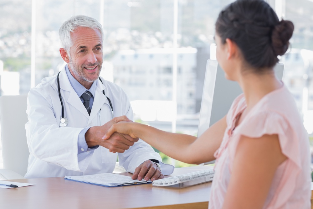 Doctor shaking hands to patient in the office at desk