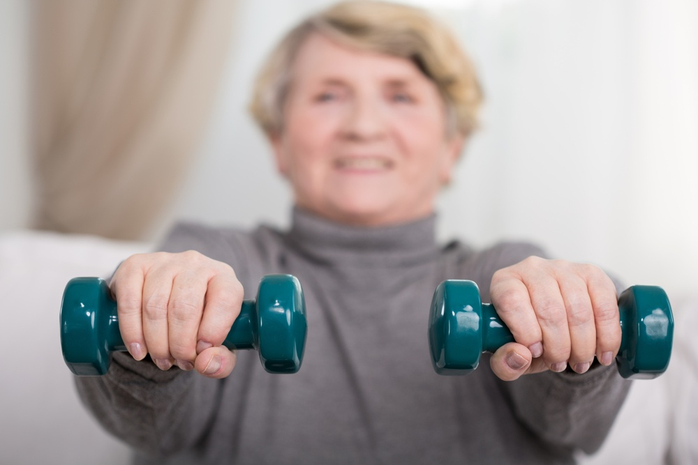 Portrait of active elder lady training with dumbbells