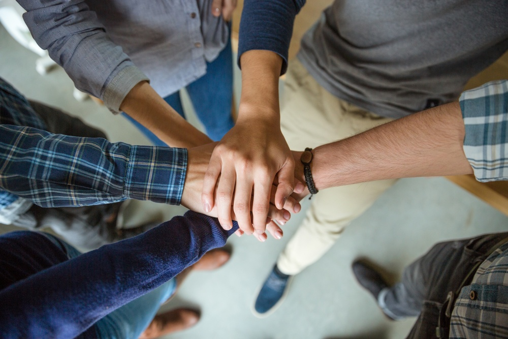 Top view of people joining hands together as a symbol of partnership.jpeg