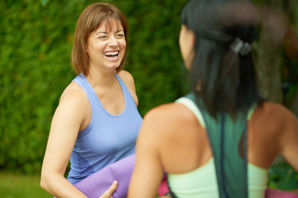 Two mature women talking before doing yoga in the summer