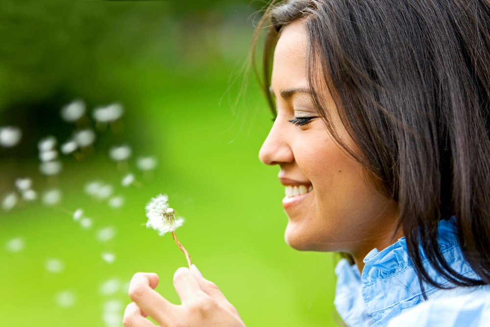 beautiful woman blowing a flower and smiling